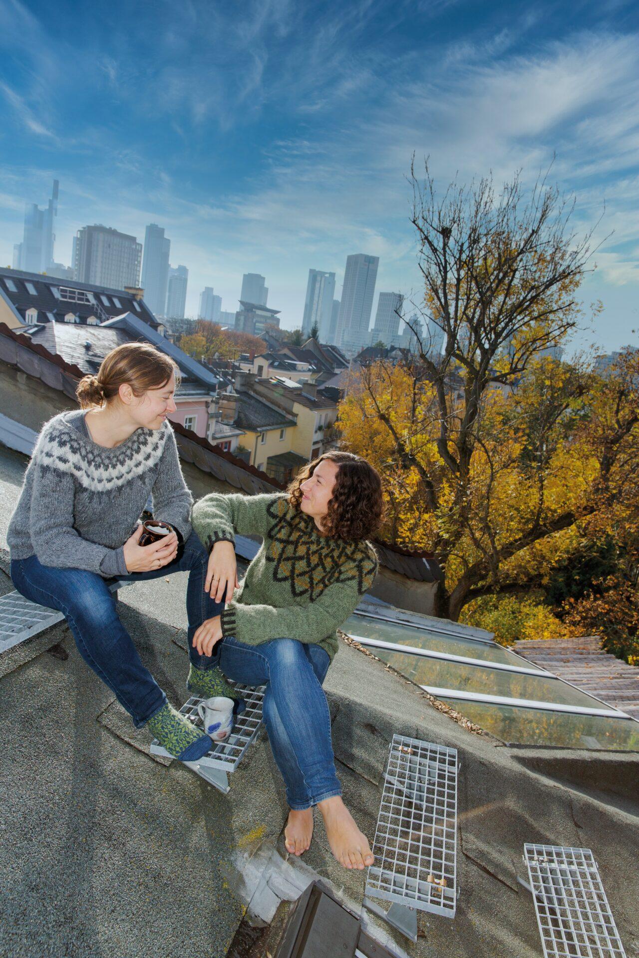Die Autorinnen Juliane und Laura im Gespräch, auf einem Stadtdach sitzend, die Skyline im Hintergrund.