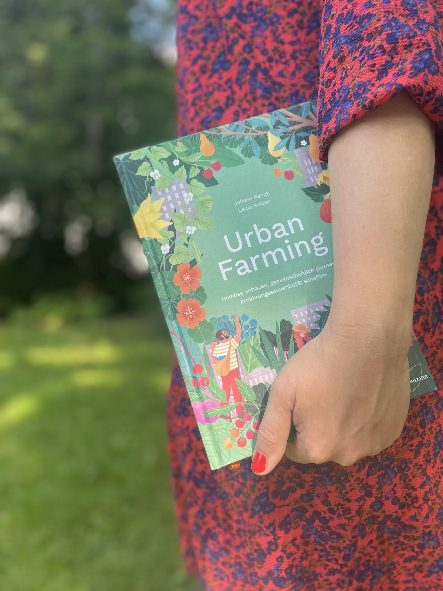 Eine Frau trägt das Buch Urban Farming im Arm.
