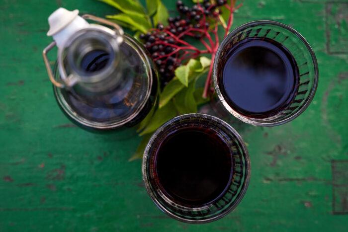 Zwei Gläser Holundersaft, eine Flasche sowie eine Dolde mit Holunderbeeren