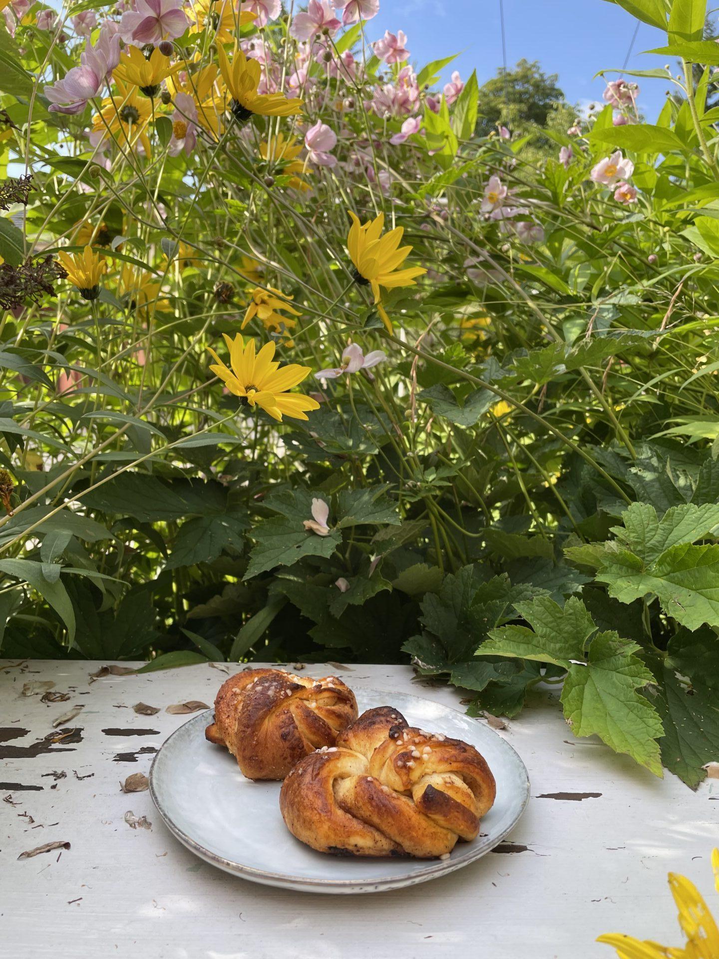 Zimtschnecken vor Blumen