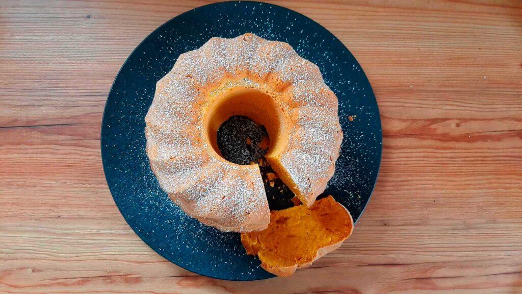 Kürbisguglhupf angeschnitten auf einer Platte mit Puderzucker